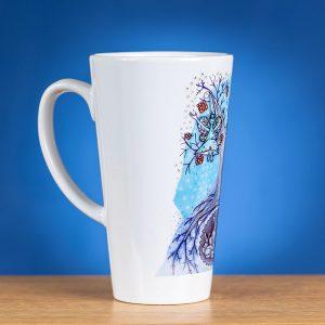 Didlis Latte puodelis su piešiniu pasuktas šonu priešais mėlyną foną