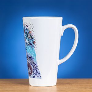 Didelis latte puodelis papuoštas originaliu piešiniu ir pasuktas šonu