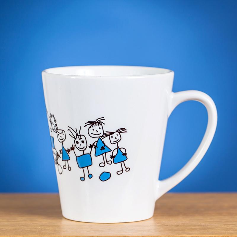 Mažas latte puodelis dekoruotas piešiniu ant gelsvo stalo priešais mėlyną foną
