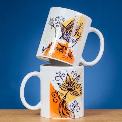 Du dekoruoti paukštelio piešiniu puodeliai sustatyti vienas ant kito