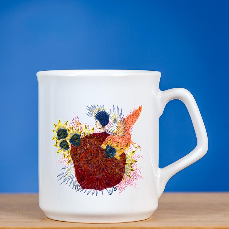 Elegantiškas puodelis su originaliu piešiniu FĖJA I priešais mėlyną foną