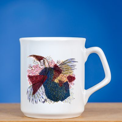 """Elegantiškas baltas puodelis su piešiniu 'FĖJA V"""" stovintis ant stalo priešais mėlyną foną"""