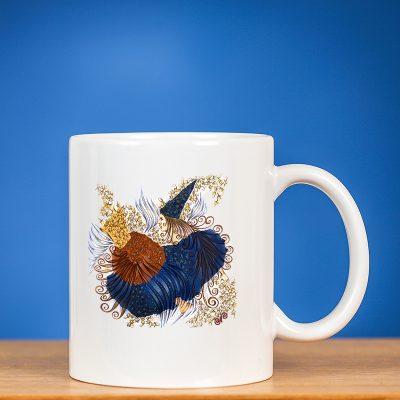"""Standartinis sublimacinis puodelis su piešiniu """"FĖJA II"""" ant stalo mėlyname fone"""